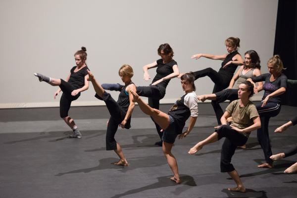 A group of dancers leaning back and leg extended high