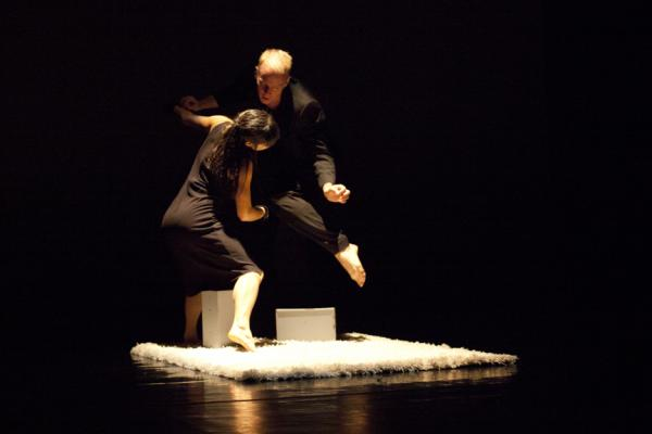 dancers stepping over box in dim light