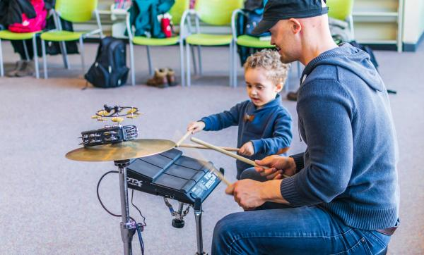 Drummer playing at live at the library with small child watching