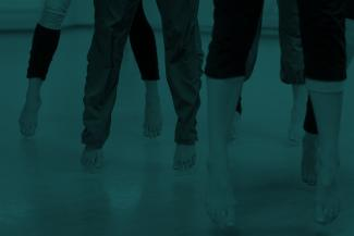Green tinted image of dancers' feet and legs mid-jump