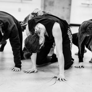 Black and White Photo - Four dancers on all fours with heads down